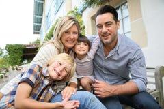 坐愉快的家庭的画象户外 库存照片