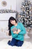 坐户内在圣诞节12月的可爱的年轻深色的妇女 库存照片