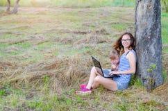 坐户外与膝上型计算机,自由空间的妈妈和女儿 图库摄影