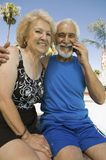 坐户外人的资深夫妇使用手机画象。 免版税库存照片