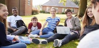 坐户外和研究项目的少年学生 免版税库存图片