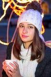 坐户外在与杯子的冬天的美丽的女孩 库存图片