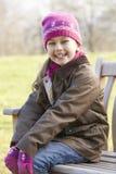 坐户外在冬天的画象女孩 免版税库存照片