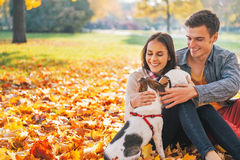 坐户外在秋天公园的愉快的年轻夫妇画象  免版税库存照片