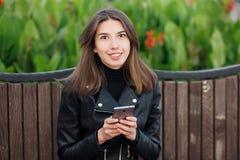 坐户外城市公园的一名年轻俏丽的微笑的深色的妇女的情感画象穿黑皮革外套使用智能手机 免版税库存图片