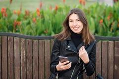 坐户外城市公园的一名年轻俏丽的微笑的深色的妇女的情感画象穿黑皮革外套使用智能手机 库存图片