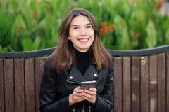 坐户外城市公园的一名年轻俏丽的微笑的深色的妇女的情感画象穿黑皮革外套使用智能手机 免版税库存照片