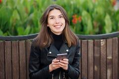 坐户外城市公园的一名年轻俏丽的微笑的深色的妇女的情感画象穿黑皮革外套使用智能手机 图库摄影