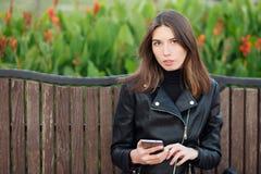 坐户外城市公园的一名年轻俏丽的深色的妇女的情感画象穿黑皮革外套使用智能手机app为 免版税图库摄影