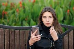 坐户外城市公园的一名年轻俏丽的深色的妇女的情感画象穿黑皮革外套使用智能手机app为 库存图片