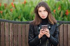 坐户外城市公园的一名年轻俏丽的深色的妇女的情感画象穿黑皮革外套使用智能手机app为 免版税库存图片