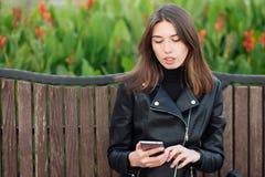 坐户外城市公园的一名年轻俏丽的深色的妇女的情感画象穿黑皮革外套使用智能手机app为 免版税库存照片