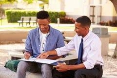 坐户外有工作的老师帮助的男学生 库存照片