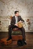 坐手提箱和演奏小鼓的商人 收集alm 库存照片