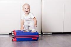 坐手提箱和看照相机的逗人喜爱的小孩 去滑稽的男婴假期 免版税库存照片