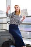 坐手提箱在火车站和拿着地图的镶边毛线衣的女孩和做selfie 免版税库存照片