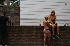坐扶手栏杆和享受党的诺丁山狂欢节美丽的愉快的夫人 库存照片