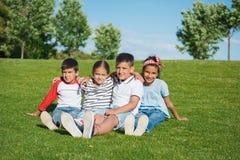 坐拥抱在绿草和微笑对照相机的不同种族的孩子 库存照片