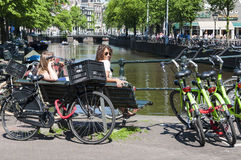 坐接近繁忙的自行车停车的荷兰语人员 免版税库存照片