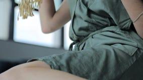 坐摇摆和显示她的腿的一件绿色礼服的俏丽的少女 影视素材