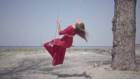 坐摇摆和看蓝色湖的一个惊人的壮观的看法前面的红色礼服的画象亭亭玉立的逗人喜爱的妇女 股票录像