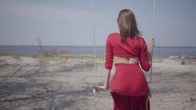 坐摇摆和看蓝色湖的一个惊人的壮观的看法红色礼服的画象亭亭玉立的端庄的妇女  影视素材