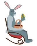 坐摇椅和拿着复活节彩蛋的灰色兔子 免版税库存图片