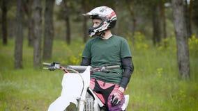 坐摩托车休息在森林地的一个年轻人,盔甲的人民享受在自然的音乐 股票视频