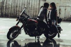 坐摩托车和看彼此的时髦的年轻夫妇 免版税库存图片