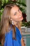 坐斜向一边与流动的头发的美丽的微笑的女孩首肩画象  免版税库存图片