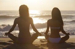 坐日落日出海滩的两个比基尼泳装妇女女孩 库存图片