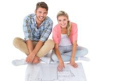 坐有吸引力的年轻的夫妇看图纸 免版税图库摄影