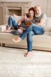 坐有数字式设备的沙发和微笑对照相机的成熟夫妇 库存图片
