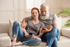 坐有数字式设备的沙发和微笑对照相机的成熟夫妇 免版税库存照片