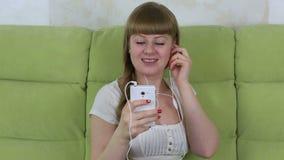 坐有智能手机的沙发和听到音乐的女孩在耳机 股票录像