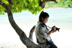 坐木材在树下和使用照相机的亚洲妇女为达 免版税库存照片