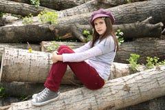 坐木材的女孩日志 免版税库存图片