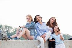 坐本质上和看照相机的四个可爱的愉快的逗人喜爱的女性朋友 库存照片