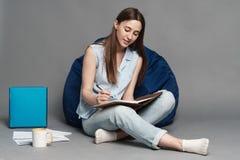 坐枕头袋子和在手上的妇女拿着一个笔记本 查出在灰色背景 免版税库存照片