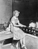 坐柜台和烹调食物的少妇在厨房里(所有人被描述不是更长的生存和没有庄园exis 库存照片