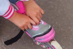 坐栏杆和投入在路辗的小女孩在公园 免版税库存照片