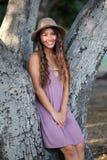 坐树的弯曲处的俏丽的女孩 免版税库存照片