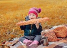 坐格子花呢披肩和吃长方形宝石的小女孩 免版税库存照片