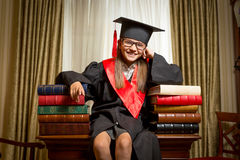 坐桌和倾斜在书的毕业盖帽的女孩 免版税库存图片
