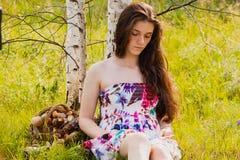 坐森林沼地和阅读书的女孩 免版税图库摄影