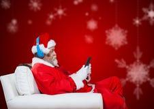 坐椅子和使用手机的圣诞老人 免版税库存图片