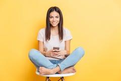坐椅子和使用智能手机的妇女 免版税图库摄影