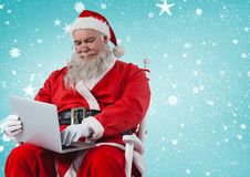 坐椅子和使用膝上型计算机的圣诞老人 免版税库存图片