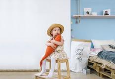 坐椅子和在家拿着一条玩具鱼的小女孩在屋子里 图库摄影