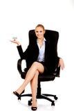 坐椅子和拿着房子的微笑的女商人塑造 免版税库存照片
